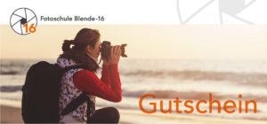 Der Blende-16 Fotokurs-Gutschein mit einer Frau, die Ihre Kamera in den Händen hält.