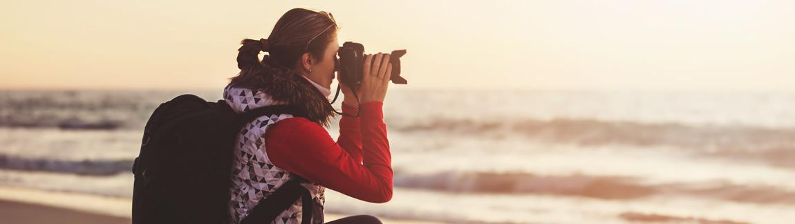 Die Frau mit Ihrer Kamera in den Händen am Meer ist das Titelbild der Seite Fotokurs-Gutschein.
