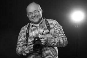 Blende-16 Trainer Herbert Mrosek mit einer Kamera in seinen Händen.