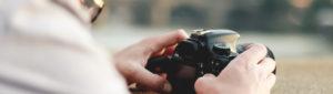 Die Person mit der Kamera in der Hand ist das Titelbild vom Blende-16 Fotokurs Einzelcoaching.